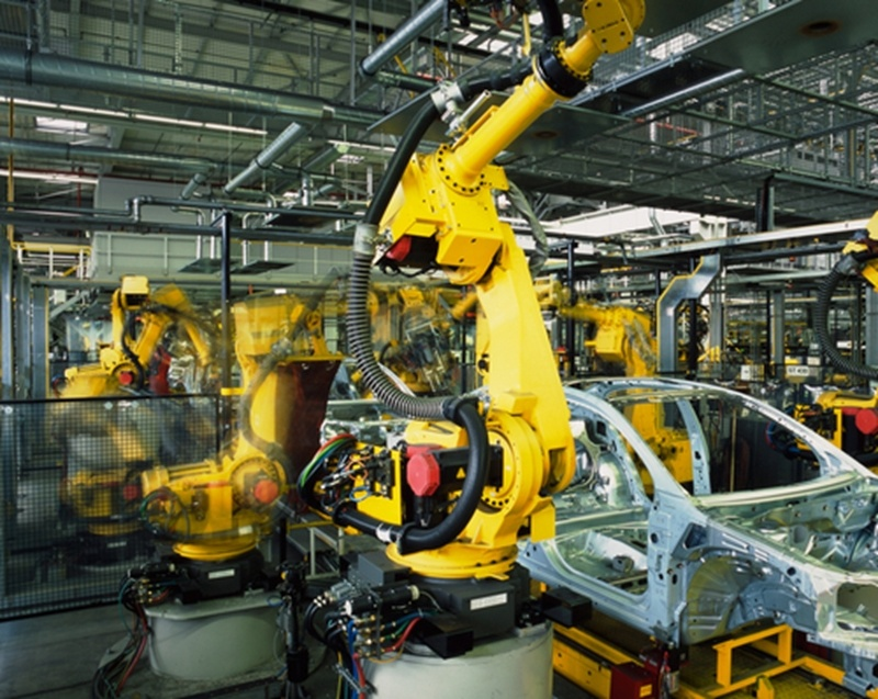 A part of an automobile is being built with a robotic arm within a manufacturing facility in Mexico