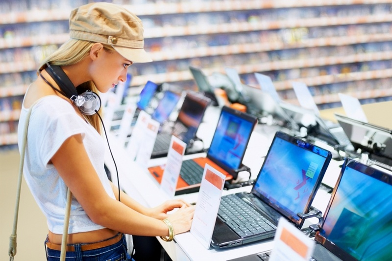 A young lady is looking at different consumer electronic goods, such as computers, at an electronics store.