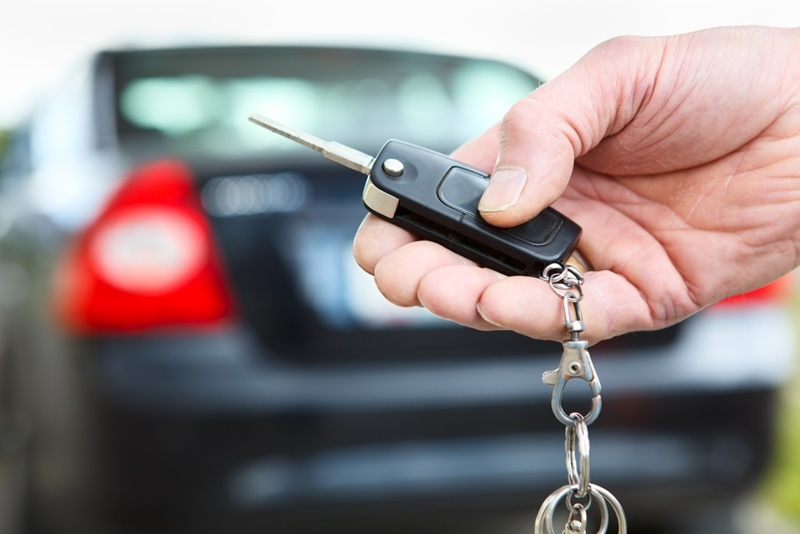 A person's hand is seen holding the keys to a new automobile while the brand new automobile is featured in the background of the picture