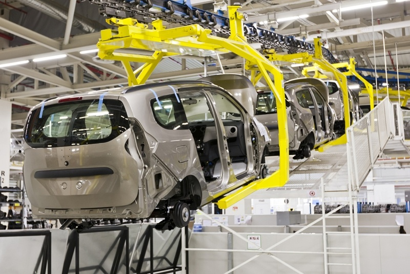 A series of automotive vehicles in the shape of minivans is being carried in the air with robotic arms inside a Mexican automobile manufacturing plant .